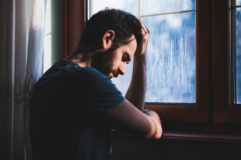 Photo of a man looking depressed next to a frost-covered window due to seasonal affective disorder.